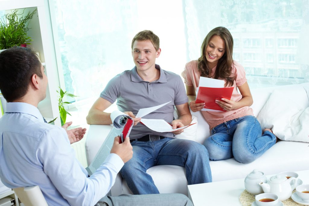 Young family reading insurance contract, their agent advising